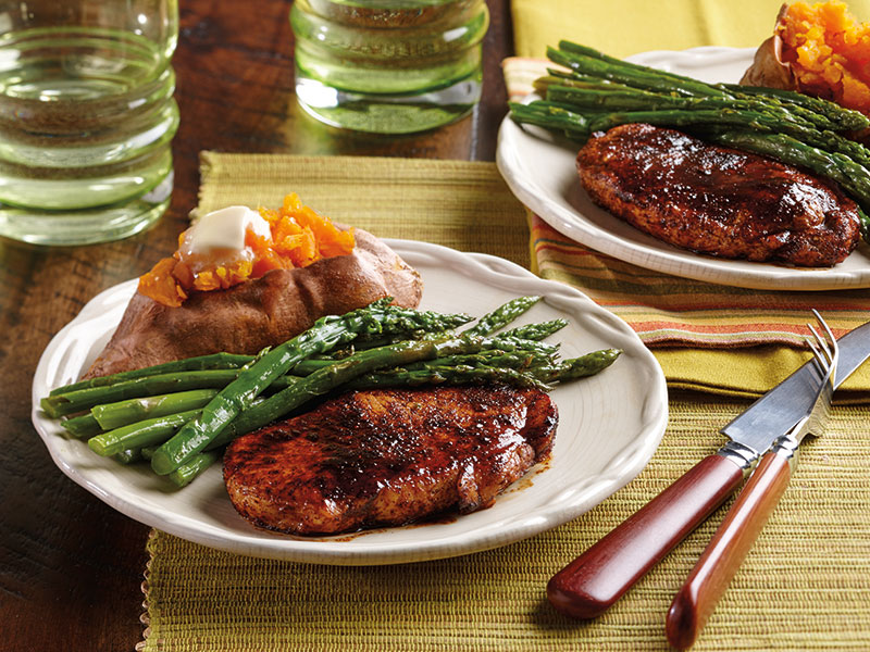 Two pork chops marinated with ancho chile honey citrus sauce with a side of sweet potatoes and asparagus